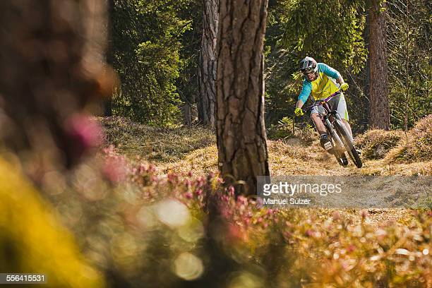 Young male mountain biker cycling downhill in forest