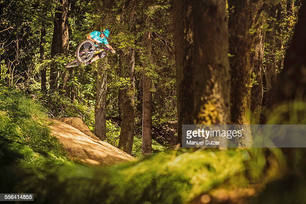 Young male mountain biker jumping mid air in forest