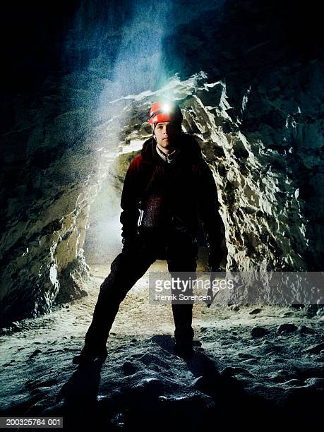 young male mountain climber standing in cave - spelunking stock pictures, royalty-free photos & images