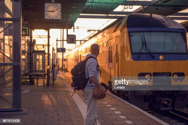 young male non-caucasian student carrying a basketball whilst waiting at a european train station on a beautiful evening - northern europe stock pictures, royalty-free photos & images
