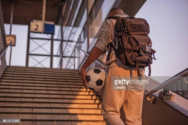 jungen männlichen nicht-kaukasischen studenten tragen einen fußball auf einem bahnhof europas auf einen schönen abend - non urban scene stock-fotos und bilder