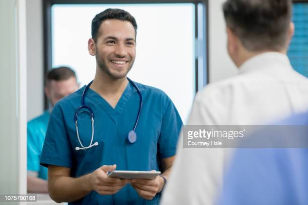young male nurse smiles while talking with coworkers in hospital emergency room - enfermeiro imagens e fotografias de stock