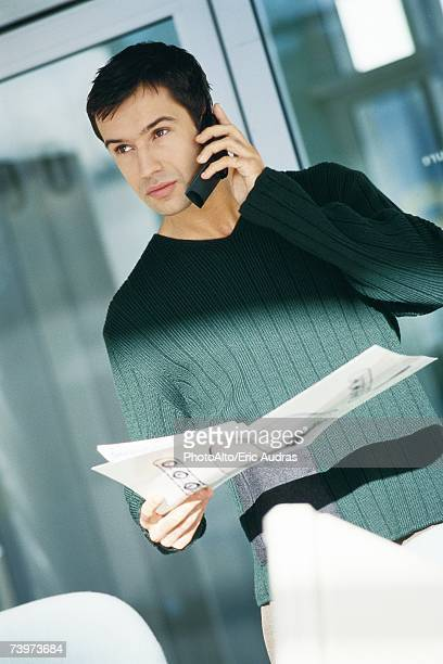 Young male office worker holding document, using telephone
