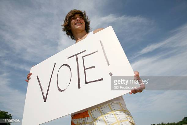 young male outside holding large sign that says vote - campaigner stock pictures, royalty-free photos & images