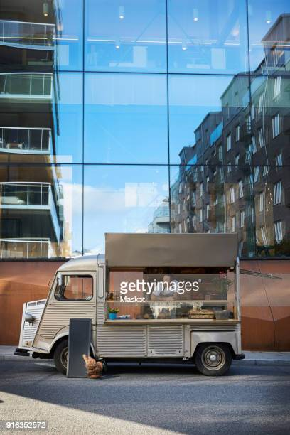 young male owner in food truck parked on city street against glass building - food truck fotografías e imágenes de stock