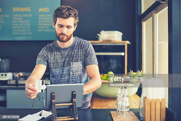 Young male owner swiping credit card on reader