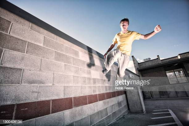 a young male parkour athlete jumping on a concrete wall in a city - robb reece stock-fotos und bilder