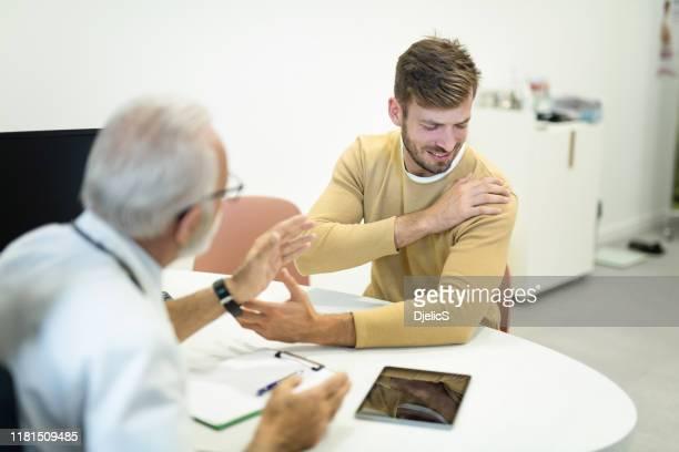 若い男性患者は、彼の医者に肩の痛みについて不平を言う。 - looking over shoulder ストックフォトと画像
