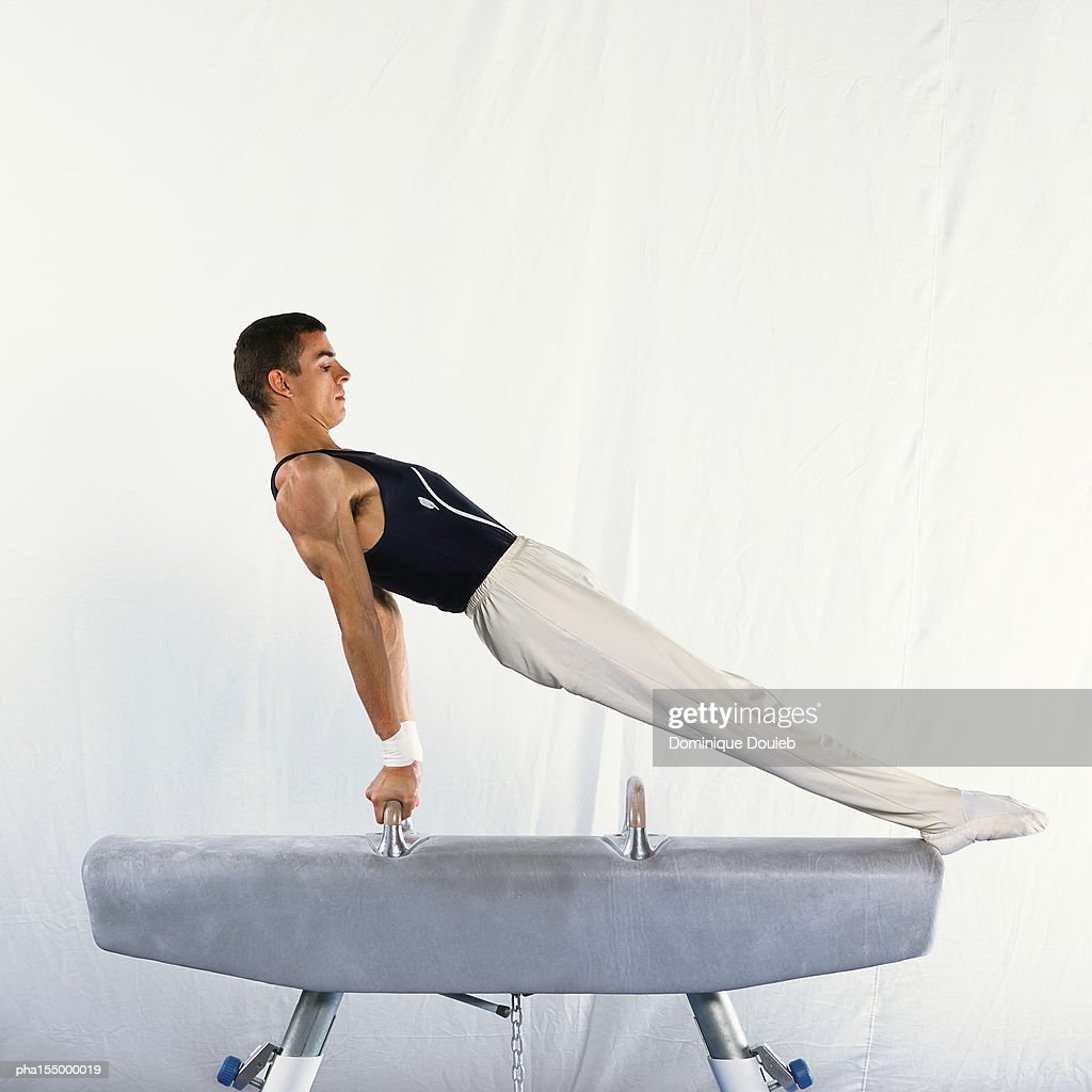 Young male performing routine on pommel horse, side view. : Stockfoto