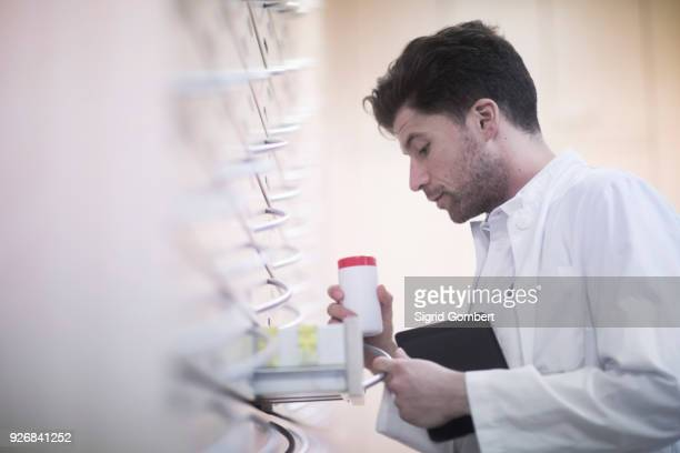 young male pharmacist removing pill bottle from pharmacy drawer - sigrid gombert stock-fotos und bilder