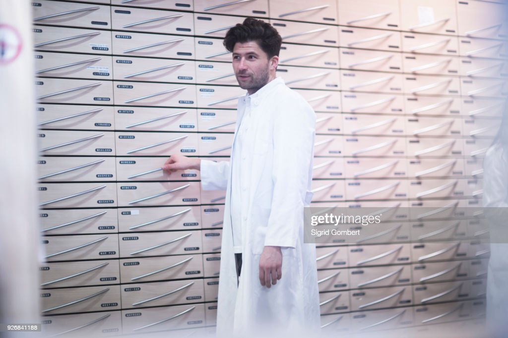 Young male pharmacist standing by pharmacy drawers : Stock-Foto