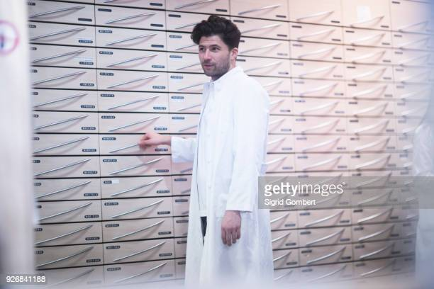 young male pharmacist standing by pharmacy drawers - sigrid gombert stock-fotos und bilder