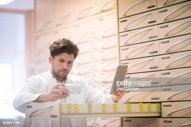 young male pharmacist using digital tablet and reading medical drug packet in pharmacy - sigrid gombert - fotografias e filmes do acervo