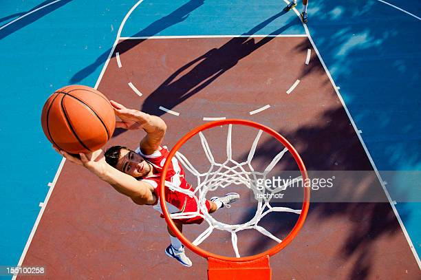 Young male player making basket