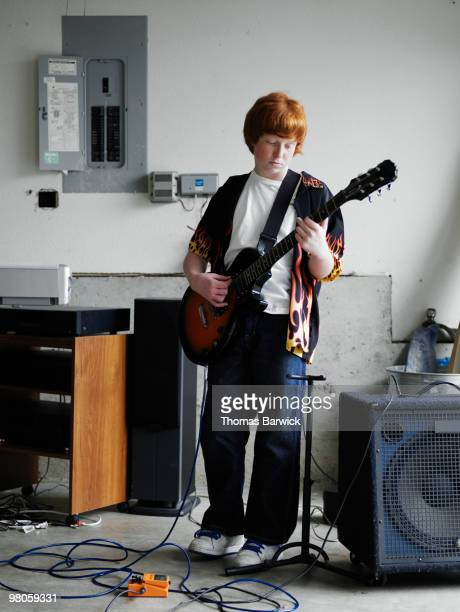 Young male playing guitar in garage of home