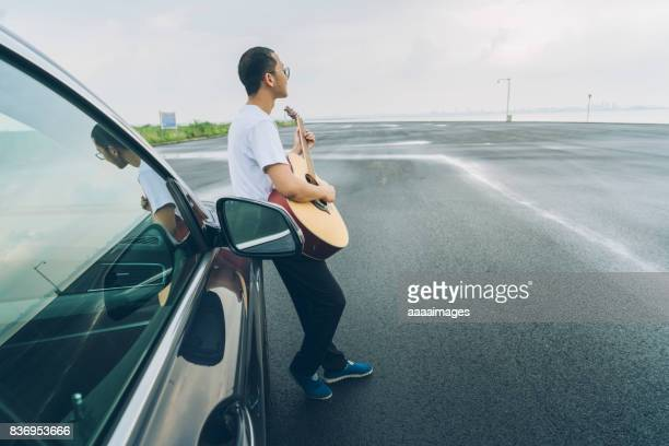 young male playing guitar leaning on automobile