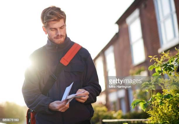 Young male postman preparing post