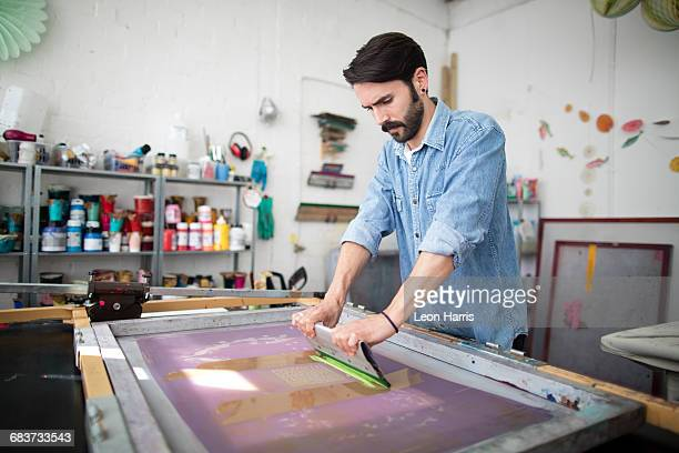 Young male printer using squeegee in printing press studio