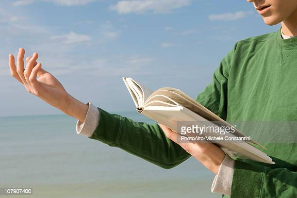 Young male reading aloud from book at the beach