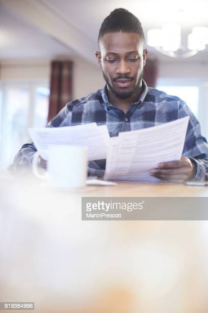 Young male reading through energy bills