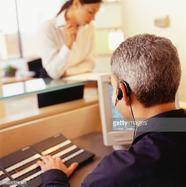 Young male receptionist wearing headset, using switchboard