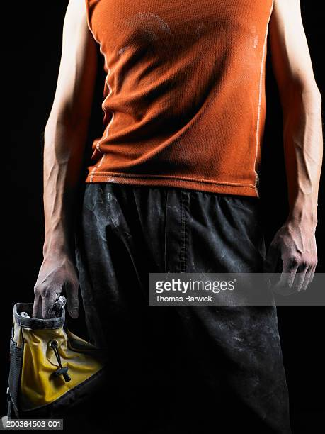 young male rock climber holding chalk bag, mid section - chalk bag stock pictures, royalty-free photos & images