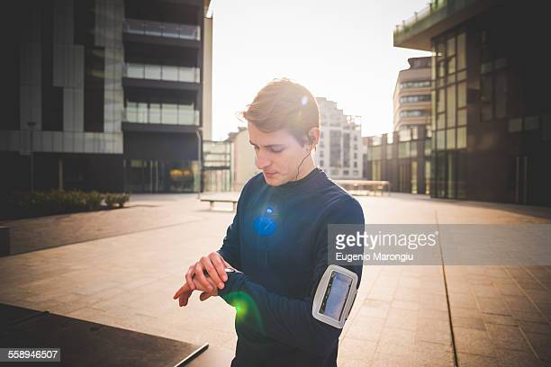 Young male runner checking wrist watch in city square