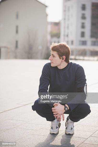 Young male runner crouching in city square