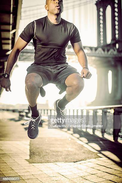 Young male runner doing exercises, New York City, USA
