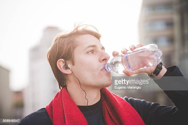 Young male runner drinking water