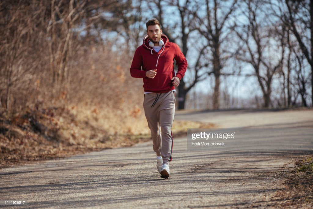 Young male runner jogging outdoors : Stock Photo