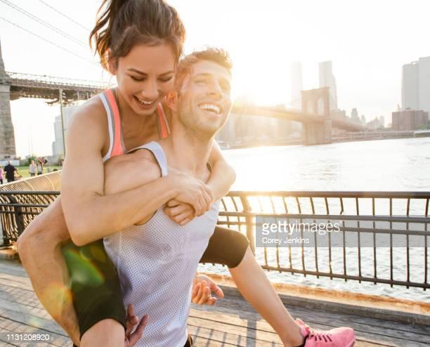 young male runner piggybacking girlfriend, new york, usa - participacion ciudadana fotografías e imágenes de stock