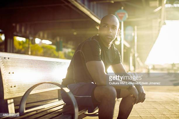 Young male runner resting on bench, New York City, USA