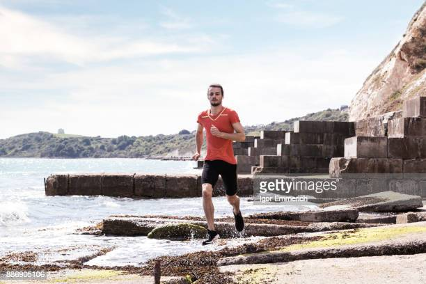 Young male runner running along waters edge of sea defence