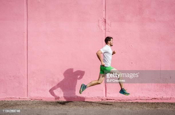 young male runner running past pink wall - corredor caraterística de construção imagens e fotografias de stock
