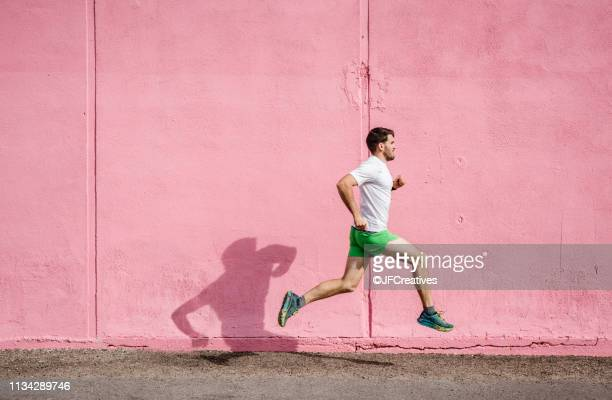 young male runner running past pink wall - ランニングショートパンツ ストックフォトと画像