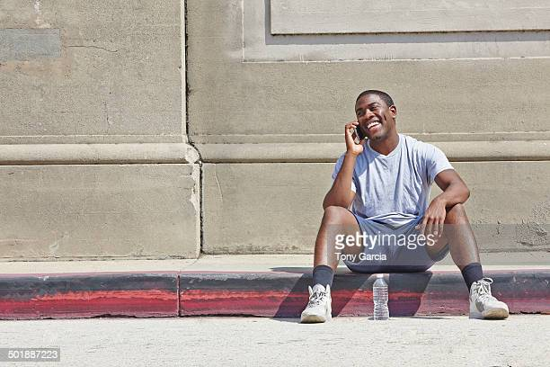Young male runner sitting on sidewalk chatting on smartphone