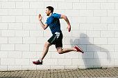 Young male runner speed running along sidewalk