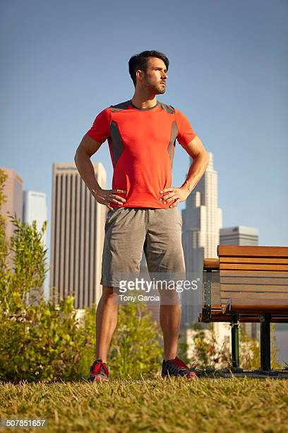 Young male runner taking a break in park