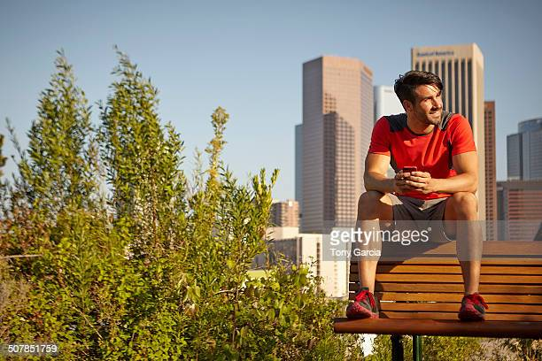 Young male runner taking a break on park bench