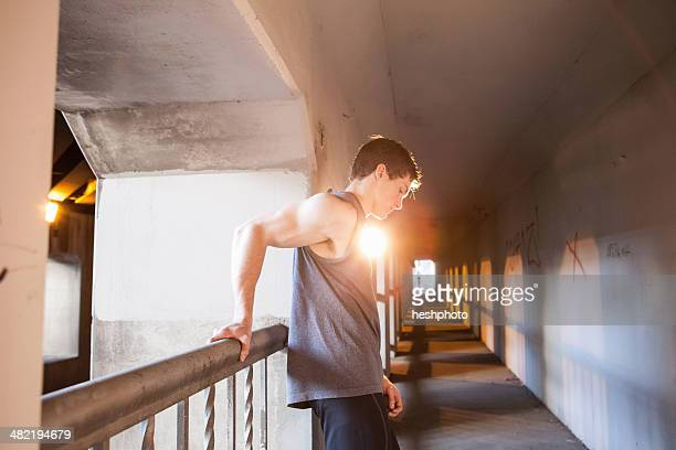 young male runner taking a break on urban bridge - heshphoto stock pictures, royalty-free photos & images