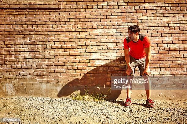 Young male runner taking a break
