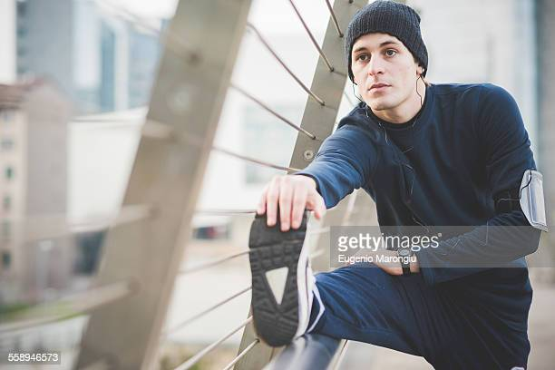 Young male runner touching toes on city footbridge