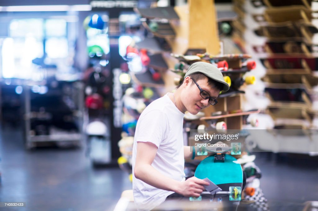 Young male sales assistant repairing skateboard at skateboard shop counter : Stock Photo