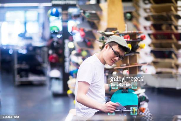 young male sales assistant repairing skateboard at skateboard shop counter - tee sports equipment stock photos and pictures