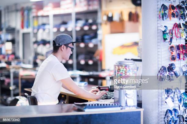 Young male sales assistant typing on computer keyboard at skateboard shop counter