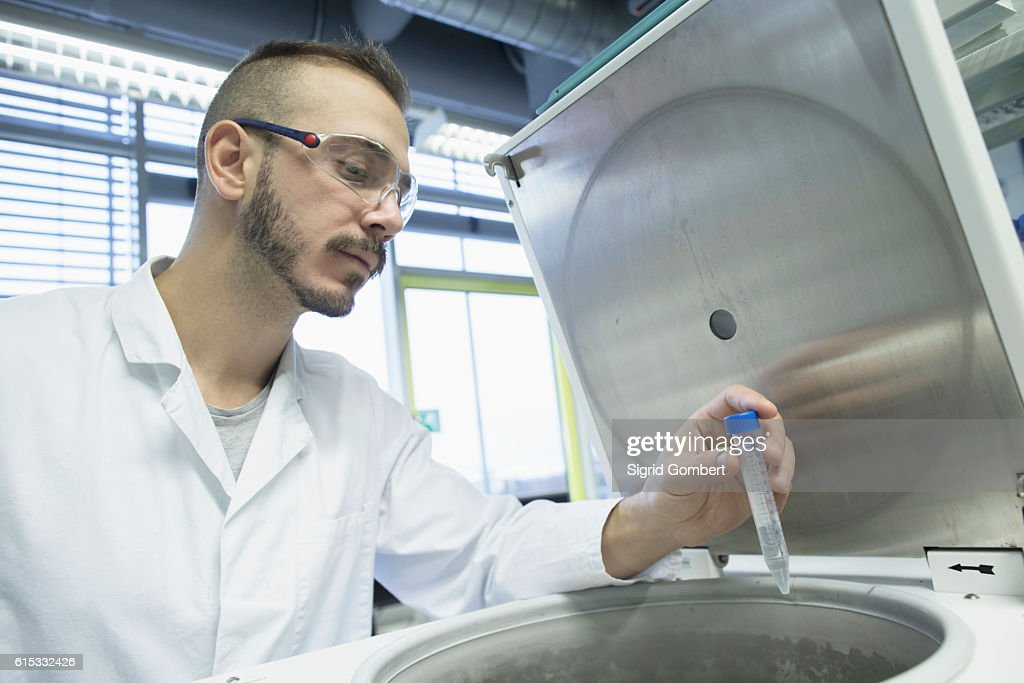 Young male scientist examining test tube in a pharmacy laboratory, Freiburg im Breisgau, Baden-Württemberg, Germany : Stock-Foto
