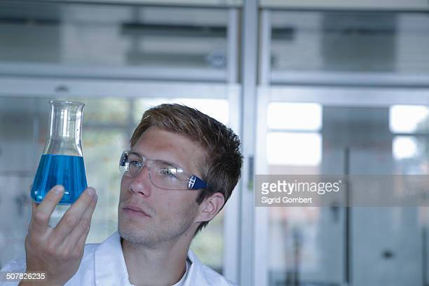 young male scientist holding up erlenmeyer flask in lab - sigrid gombert stock pictures, royalty-free photos & images