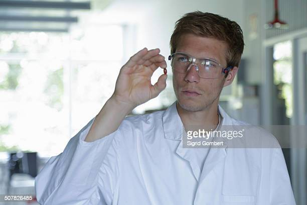 young male scientist holding up pill in lab - sigrid gombert stock pictures, royalty-free photos & images