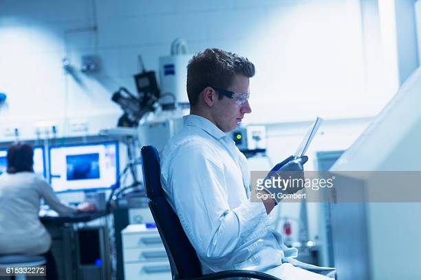 young male scientist looking at report in an optical laboratory, freiburg im breisgau, baden-württemberg, germany - sigrid gombert 個照片及圖片檔